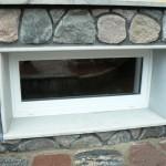 Окно в цоколе, отделанное камнем